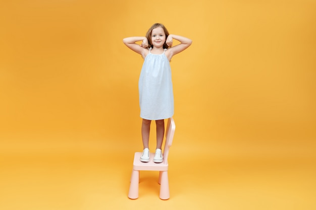 Little girl is standing on the chair and showing strong arms