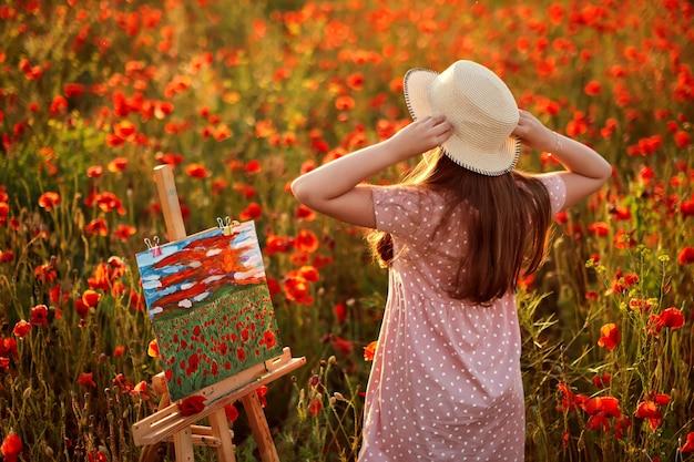 Маленькая девочка стоит в поле красных маков, рисует пейзаж и любуется закатом.