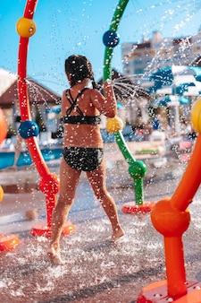 小さな女の子が背中を背負って立ってプールに立っている黒い水着の幸せな美しい女の子が水で遊ぶ...