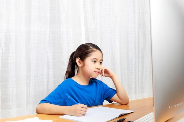 Маленькая девочка учится онлайн через интернет сидит и пишет