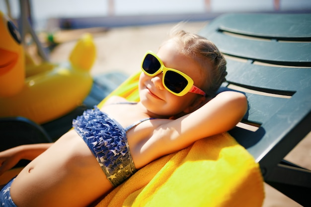 Little girl is sunbathing on a sunbed near the pool at the resort