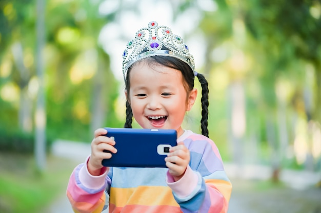 Little girl is taking a selfie , when she crowned the princess on head her smile with happy face