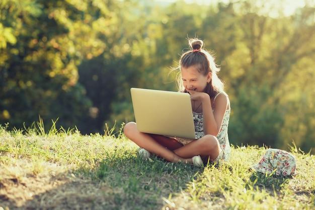 Маленькая девочка говорит на ноутбуке, сидя на траве в солнце. одет в сарафан и шляпу