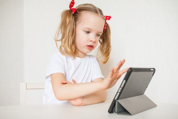 Little girl is talking online. home schooling