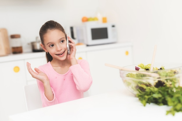 Little girl is talking on the phone in the kitchen.