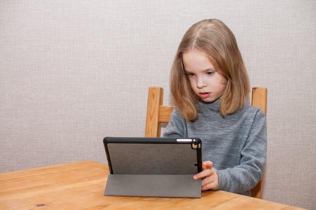 어린 소녀가 온라인 비디오 자습서를보고 있습니다. 원격 교육. 블로그. 고품질 사진