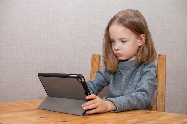 어린 소녀가 온라인 비디오 튜토리얼을보고 있습니다. 원격 교육.