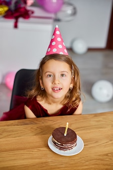 A little girl is wearing a birthday hat makes a wish, looking at a birthday cake