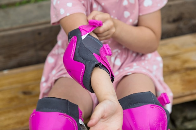 A little girl is wearing protection for roller skating sitting on the steps of her country house
