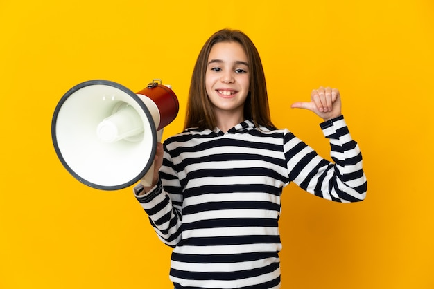 Little girl isolated holding a megaphone and proud and self-satisfied Premium Photo