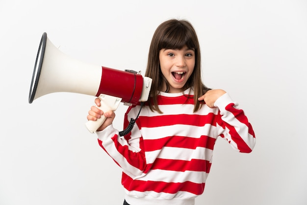 Little girl isolated holding a megaphone and with surprise facial expression