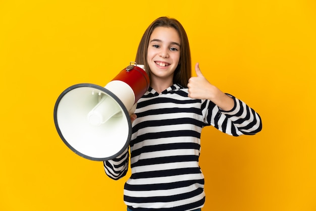 Little girl isolated holding a megaphone with thumb up Premium Photo