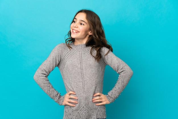 엉덩이에 팔을 포즈와 미소 파란색 벽에 고립 된 어린 소녀