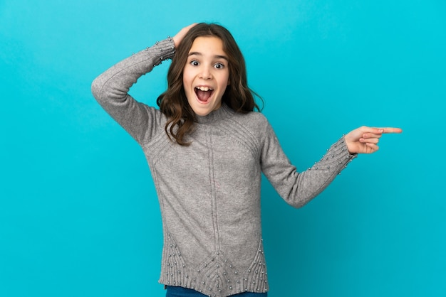 파란색 벽에 고립 된 어린 소녀 놀라게 하 고 측면에 손가락을 가리키는