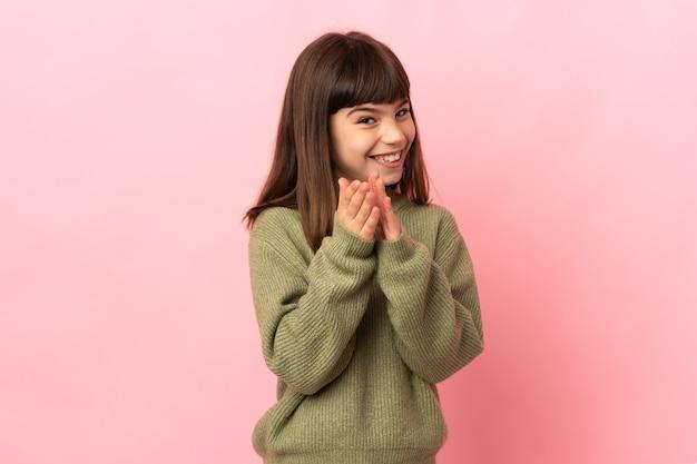 Маленькая девочка изолирована на розовом и аплодирует после презентации на конференции