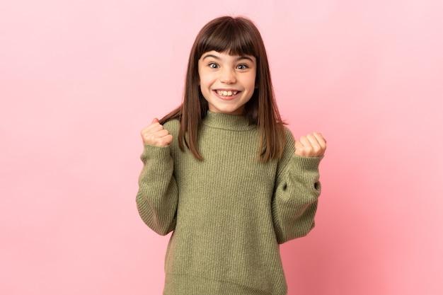 승자 위치에서 승리를 축하 분홍색 배경에 고립 된 어린 소녀