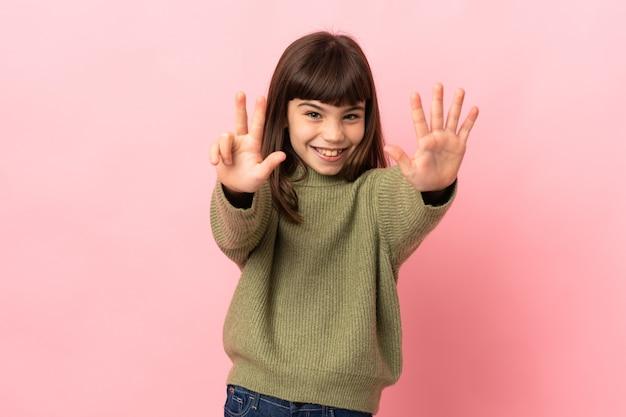 Маленькая девочка, изолированные на розовом фоне, считая восемь пальцами