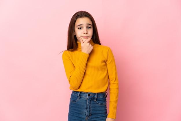 Маленькая девочка, изолированные на розовом фоне с сомнениями