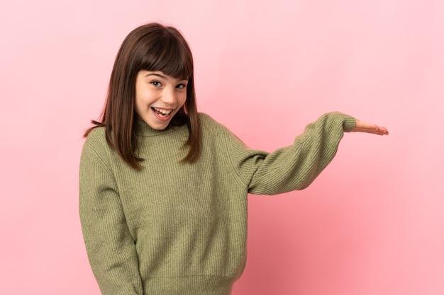 Маленькая девочка изолирована на розовом фоне, держа на ладони воображаемое пространство, чтобы вставить рекламу