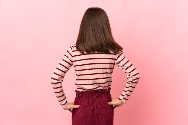 後ろの位置でピンクの背景に分離された少女