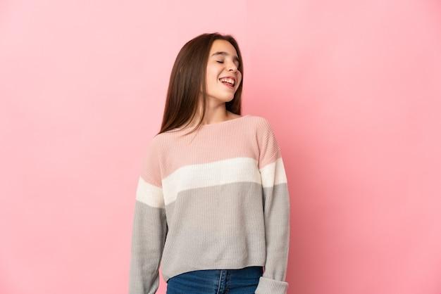 Маленькая девочка, изолированные на розовом фоне смеясь
