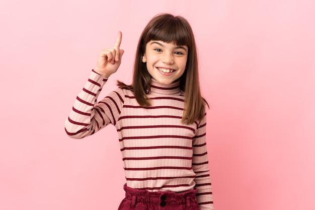 Маленькая девочка изолирована на розовом фоне, указывая вверх отличная идея