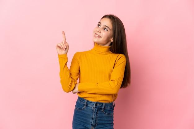 좋은 아이디어를 가리키는 분홍색 배경에 고립 된 어린 소녀