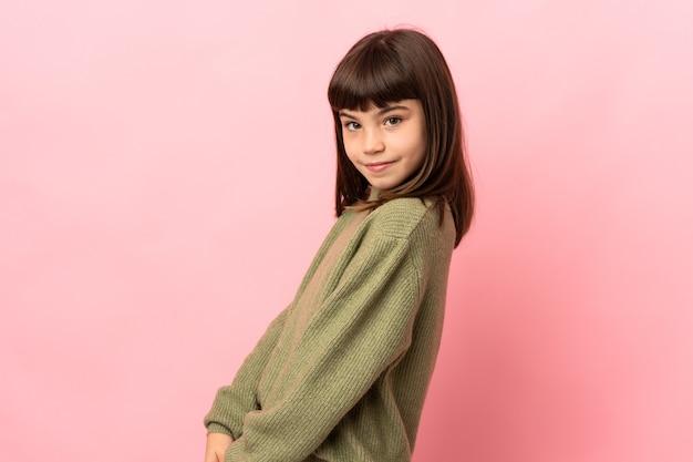 분홍색 배경에 고립 된 어린 소녀입니다. 초상화