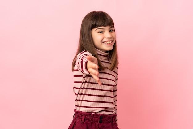 좋은 거래를 닫기 위해 악수 분홍색 배경에 고립 된 어린 소녀