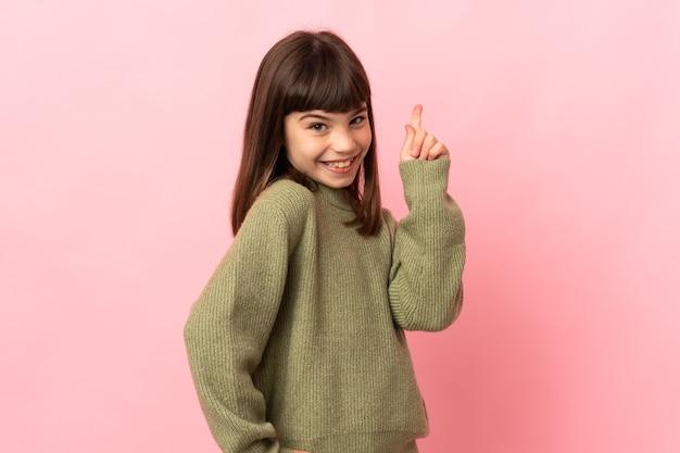 분홍색 배경에 고립 된 어린 소녀 표시 및 최고의 기호에 손가락을 들어