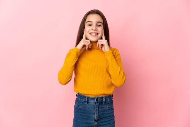 Маленькая девочка изолирована на розовом фоне, улыбаясь счастливым и приятным выражением лица