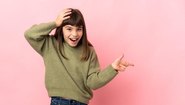 Маленькая девочка, изолированная на розовом фоне удивлена и показывает пальцем в сторону