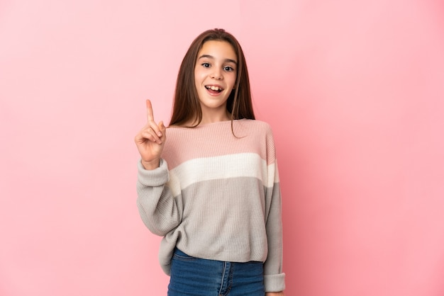 Маленькая девочка изолирована на розовом фоне, думая об идее, указывая пальцем вверх