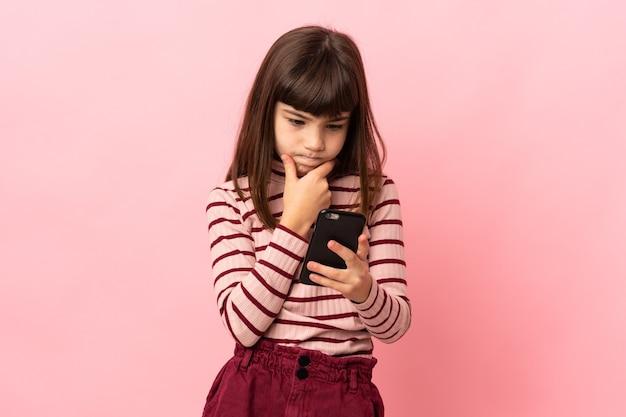 생각 하 고 메시지를 보내는 분홍색 배경에 고립 된 어린 소녀