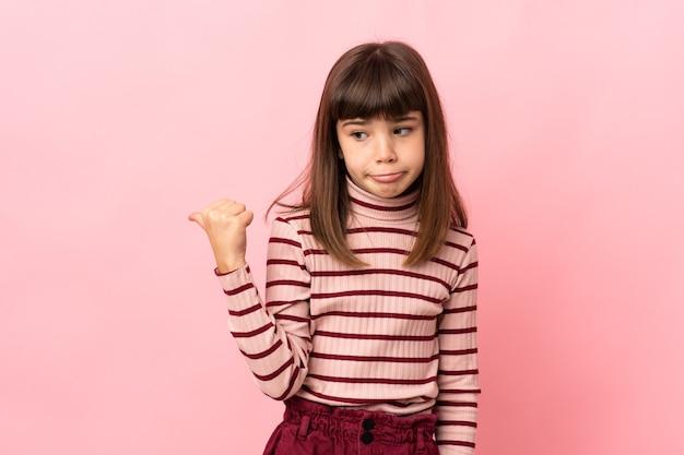 ピンクの背景に孤立した少女は不幸で横を指しています