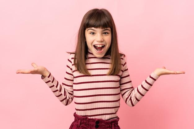 Маленькая девочка изолирована на розовом фоне с шокированным выражением лица