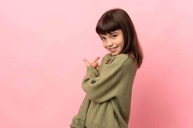 Маленькая девочка изолирована на розовом, указывая назад