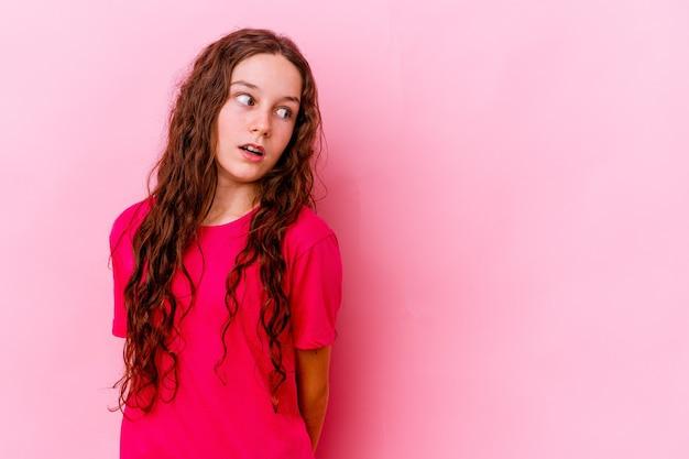 Маленькая девочка изолирована на розовой стене в шоке из-за чего-то, что она видела