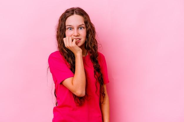 Маленькая девочка изолирована на розовой стене, кусая ногти, нервная и очень взволнованная