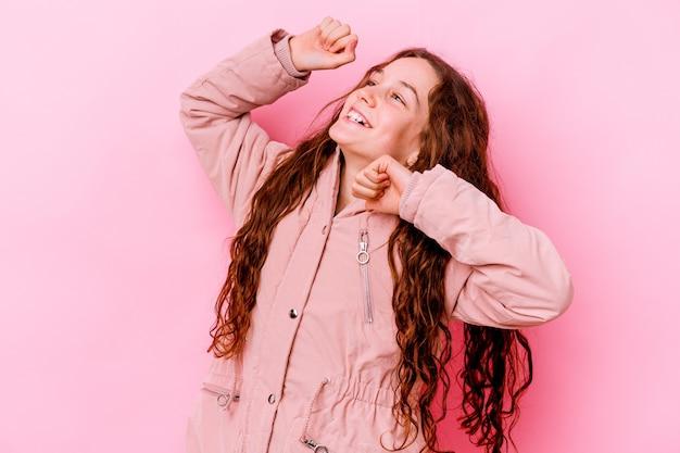 特別な日を祝うピンクの壁に孤立した少女は、エネルギーでジャンプして腕を上げる
