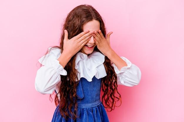 분홍색 벽에 고립 된 어린 소녀는 손으로 눈을 덮고 미소는 놀라움을 크게 기다리고 있습니다.