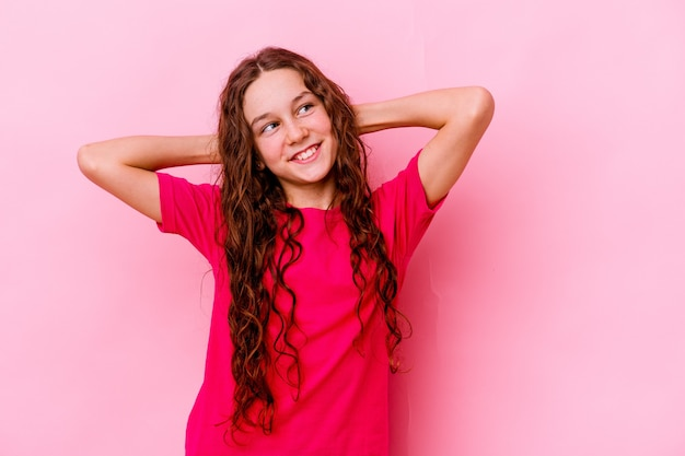 머리 뒤에 손으로 자신감을 느끼고 분홍색 벽에 고립 된 어린 소녀