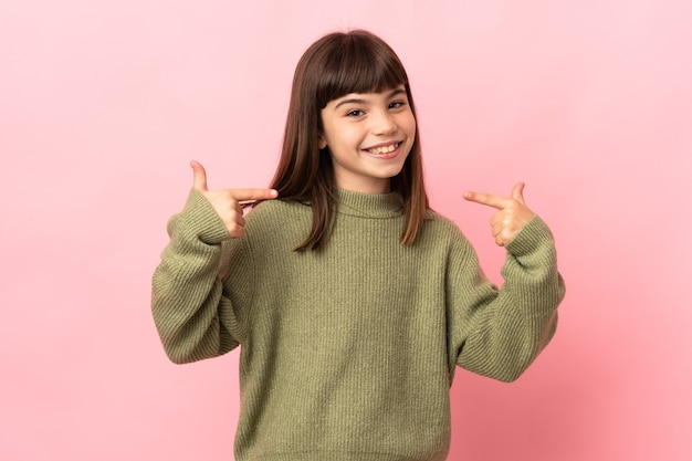 제스처를 엄지 손가락을주는 분홍색 벽에 고립 된 어린 소녀