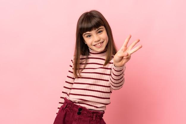 핑크 벽 행복하고 손가락으로 세 세에 고립 된 어린 소녀