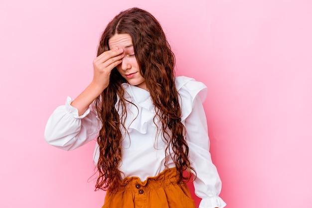 Маленькая девочка изолирована на розовой стене с головной болью, касаясь передней части лица