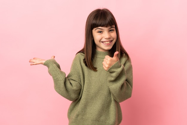 広告を挿入し、親指を立てて手のひらに架空のコピースペースを保持しているピンクの壁に孤立した少女