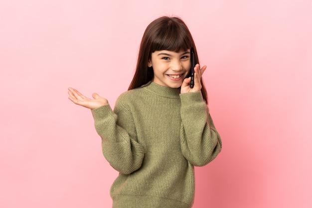누군가와 휴대 전화로 대화를 유지하는 분홍색 벽에 고립 된 어린 소녀