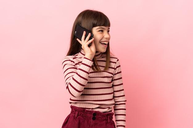 휴대 전화와 대화를 유지하는 분홍색 벽에 고립 된 어린 소녀