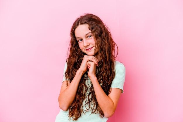 분홍색 벽에 고립 된 어린 소녀는 턱 밑에 손을 유지하고 행복하게 옆으로 찾고 있습니다.