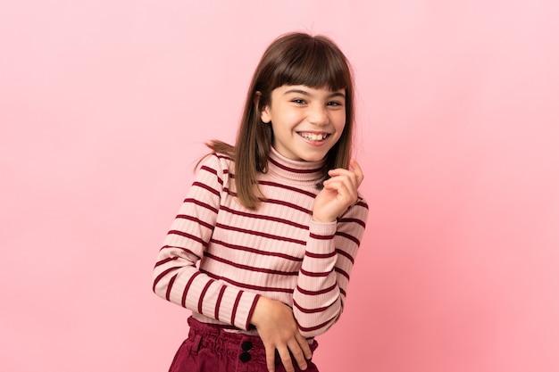 Маленькая девочка, изолированные на розовой стене смеясь